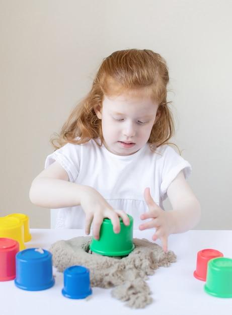Маленькая кавказская девочка, играющая с кинетическим песком в домашних условиях раннее образование подготовка к развитию школы игра для детей Premium Фотографии