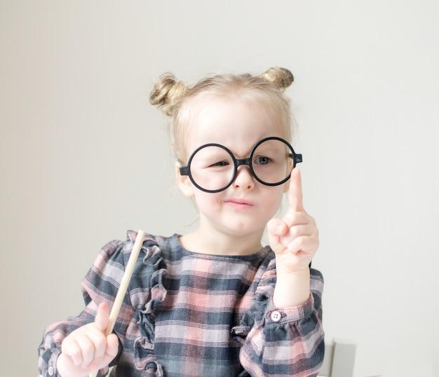 丸いメガネの白人少女。小さな先生。面白いメガネユーモア。レトロなスタイル Premium写真