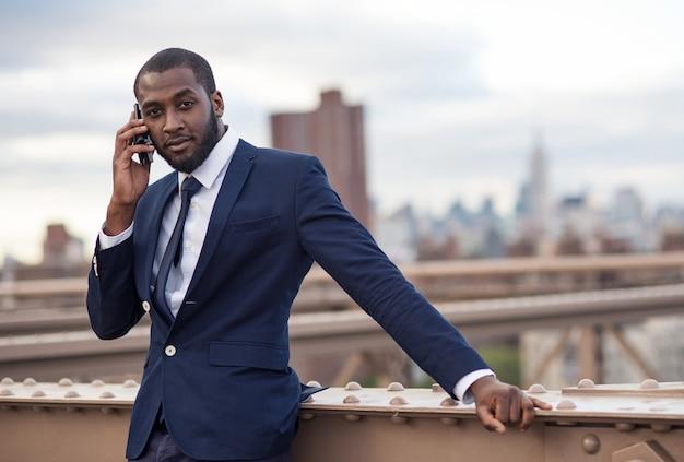 ブルックリン橋の上の電話で話している青年実業家。ニューヨーク市。 Premium写真