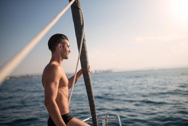 日没時の帆船の若い魅力的な男の肖像画。本物のライフスタイルイメージ。 Premium写真