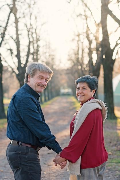 ロマンチックな年配のカップルの肖像画は屋外で一緒に公園を散歩します。 Premium写真
