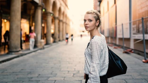 イタリアのボローニャで屋外の若い美しいブロンドの女性ライフスタイルの肖像画。ナチュラルフレア Premium写真
