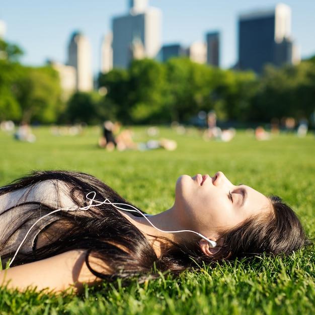 若い女性は芝生の上に敷設し、音楽を聴くセントラルパークでリラックス。ニューヨーク市。 Premium写真