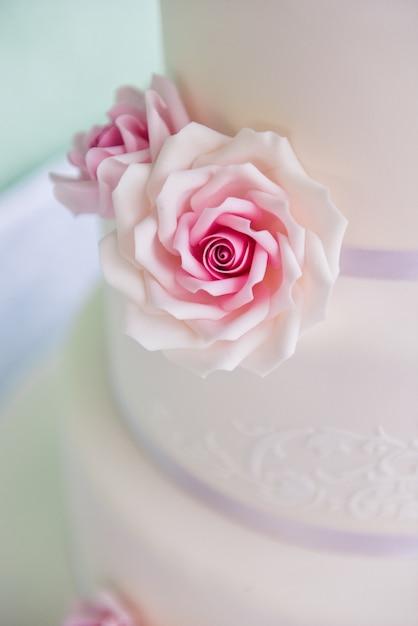 Трехъярусный свадебный торт с розовыми розами из мастики стоит на столе Premium Фотографии