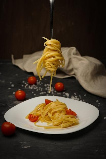 チェリートマトと暗闇の上の皿にイタリアのパスタ Premium写真