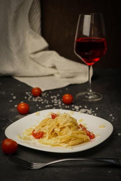 Итальянская паста на темной тарелке с помидорами черри Premium Фотографии