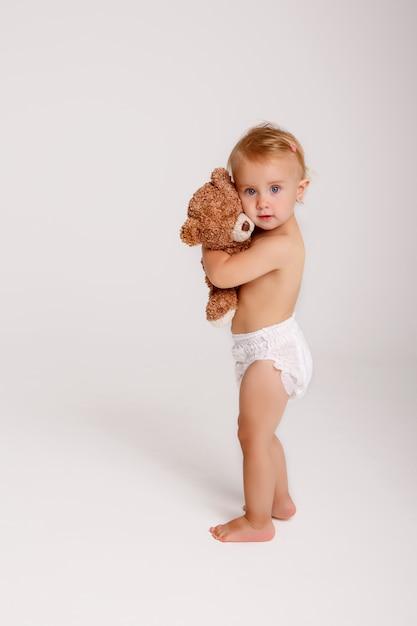 白のテディベアと遊ぶおむつの女の赤ちゃん Premium写真