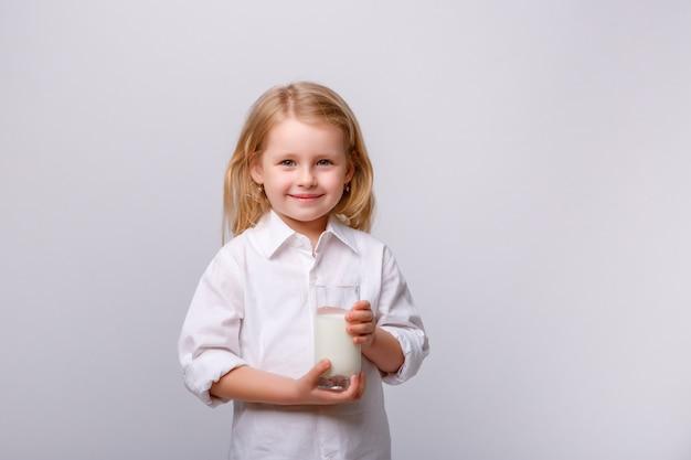 メガネと牛乳のグラスと小さな幸せな少女の肖像画。 Premium写真