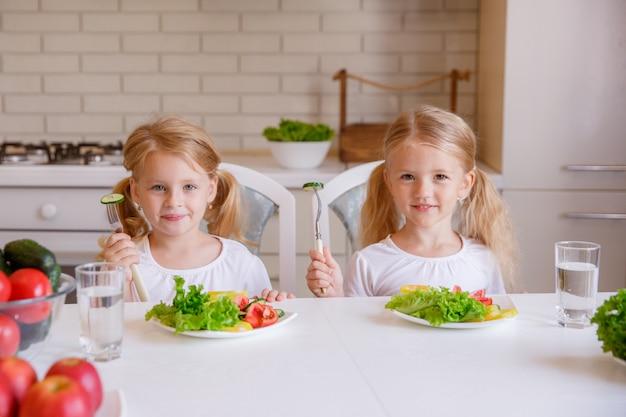 子どもたちは台所で健康食品を食べる Premium写真