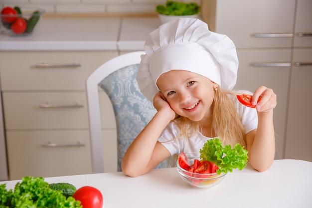 野菜を食べるキッチンでシェフの帽子の金髪の子 Premium写真