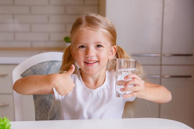 登録して親指を示し、透明なガラスを保持している女の子。子供は飲料水を勧めます。子供のための良い健康的な習慣。医療コンセプト Premium写真