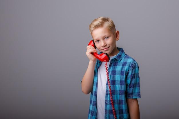 Портрет мальчика разговаривает по старому телефону Premium Фотографии
