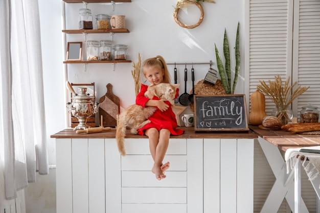 小さな女の子が家の台所で子猫と遊ぶ。人間の家族とペットの概念 Premium写真