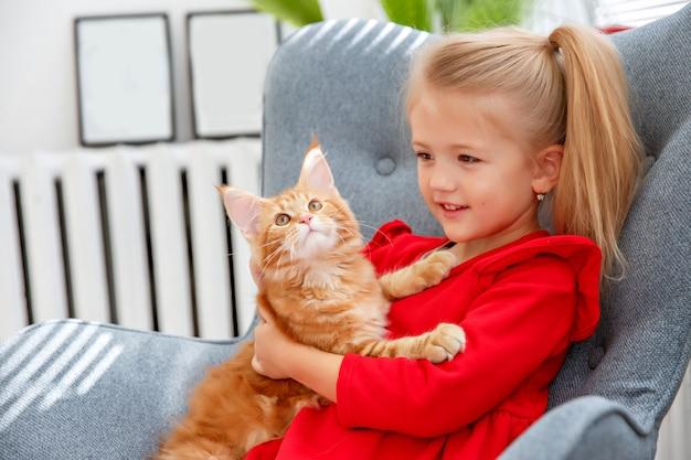 Девушка сидит в кресле с кошкой Premium Фотографии