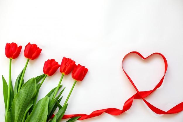 赤いチューリップとリボンハート。バレンタインデー、母の日、結婚式、女性の日のコンセプト Premium写真