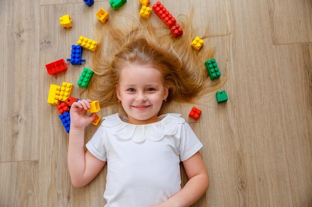 Маленькая блондинка лежит на полу среди строителей. вид сверху. Premium Фотографии