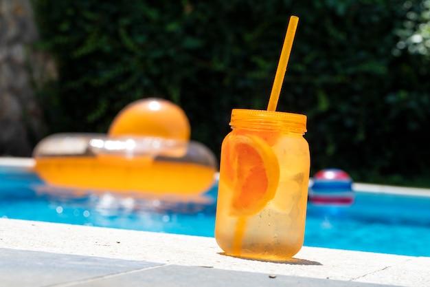 夏の冷たい飲み物。スイミングプールのボード上のオレンジ色の石工の瓶 Premium写真