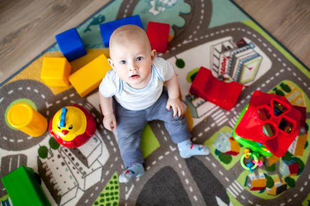 Милый маленький ребенок, играя с красочными блоками Premium Фотографии