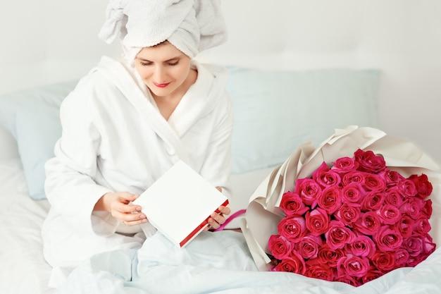 若い女性は、ベッドのギフトボックスにジュエリーとバラの花束を見つけました。花の臭いがする幸せな女の子。バレンタインデーのサプライズ Premium写真