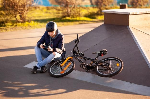 日没のヘルメットのアスファルトの上に自転車スタンドに座っている女の子 Premium写真