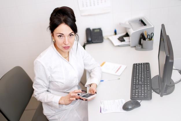Доктор молодой женщины разговаривает по телефону и что-то пишет в своем офисе Premium Фотографии