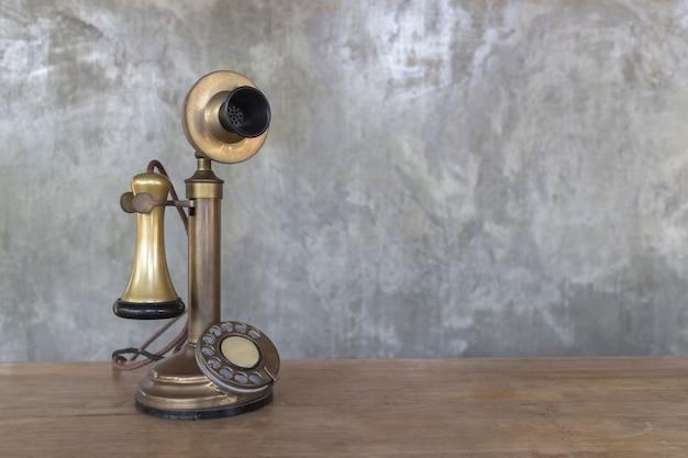 セメント壁の背景、コピースペースを持つイメージの木製のテーブルの上のヴィンテージの電話。 Premium写真