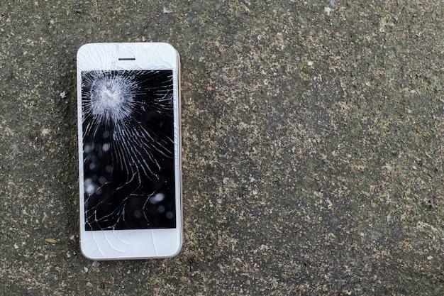 スマートフォンモバイルタッチスクリーン仲間とセメントの床に落ちる Premium写真