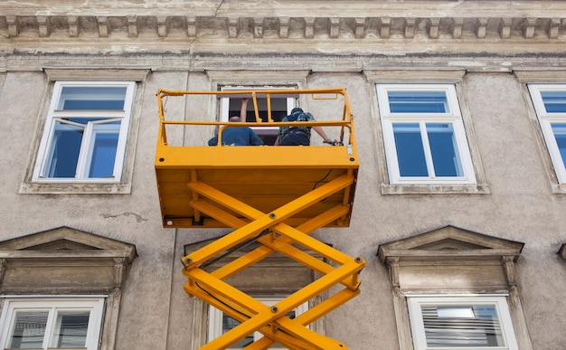 チェリーピッカーの労働者は建物のファサードを一新します Premium写真