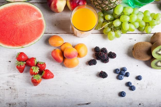 白い木製のテーブルに様々な果物 Premium写真