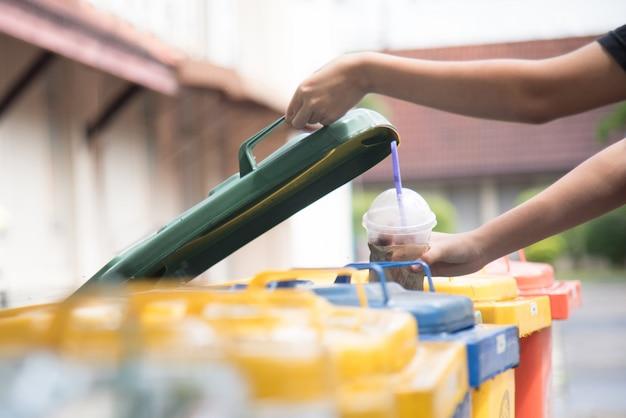 子供の手がゴミ箱に空のペットボトルを投げます。 Premium写真