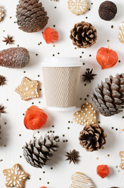 クッキー、マツ円錐形および他のクリスマスの装飾の間の持ち帰り用の紙のコーヒーカップ。上面図 Premium写真