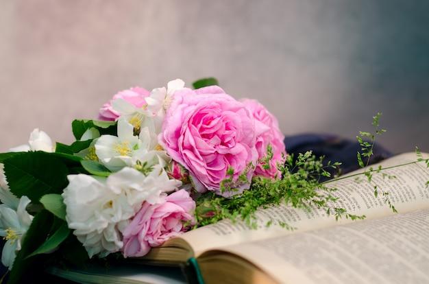 古い木製の古い本と穏やかなピンクのバラの花束。 Premium写真