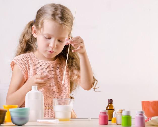 スライムグッズを作る愛らしい少女は、人気の自作グッズの材料をメッシュします。 Premium写真