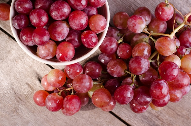 Закройте вверх по зрелому пуку красной виноградины на старой деревянной поверхности. темное угрюмое фото розового винограда в миску. Premium Фотографии