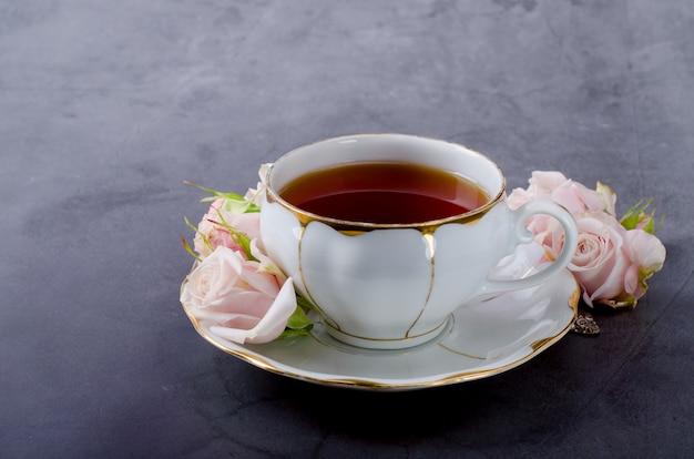 ビンテージ白磁ティーカップ、優しいピンクのバラとお茶の時間の背景 Premium写真