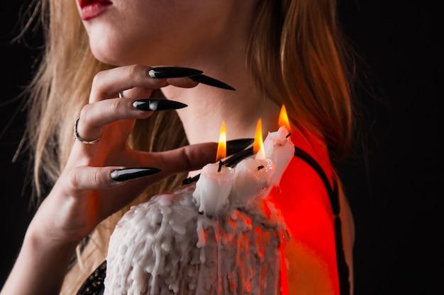 魔女の長い髪の少女が火をつけようとしている Premium写真