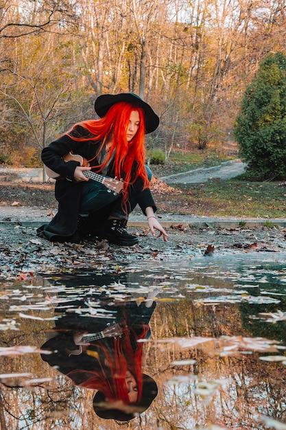 Рыжая девушка с длинными волосами играет на гавайской гитаре в парке. школа, концепция музыкального образования, студент учится играть на струнном инструменте. Premium Фотографии