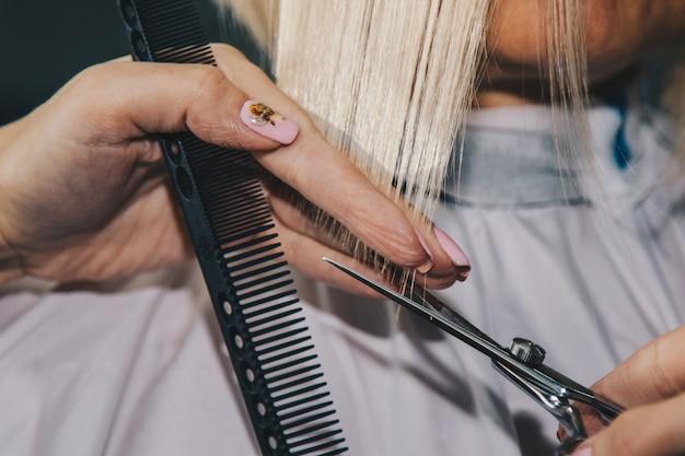 美容師のクローズアップは、サロンでクライアントの濡れた白い髪をカットします。美容師は女性をカットします。ハサミで髪を切る手の側面図です。 Premium写真