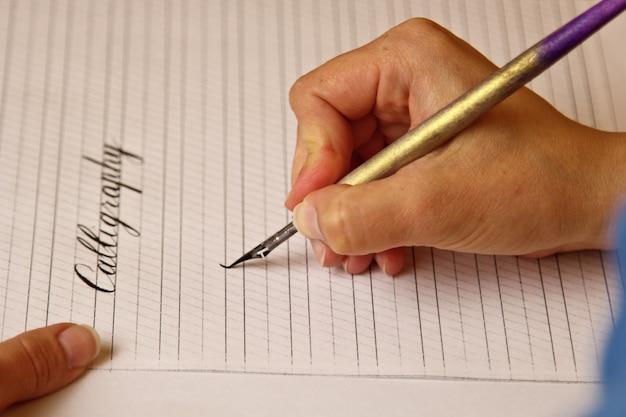 女性の手が真っ黒なペンでストライプと紙のシートに単語書道を書き込みます。 Premium写真