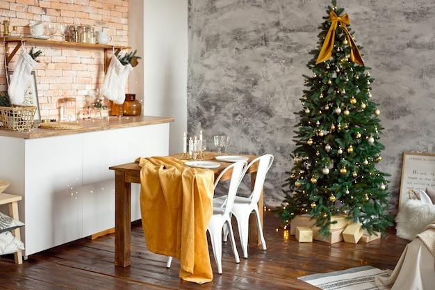 スカンジナビア風の美しいお祭りの装飾が施された部屋、テーブルのあるお祝いテーブル、その下にプレゼントのあるクリスマスツリー。 Premium写真