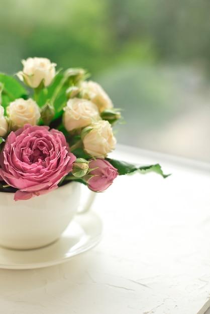 ウィンドウの反対側の白いテーブルの上にカップに白いバラの花束 Premium写真