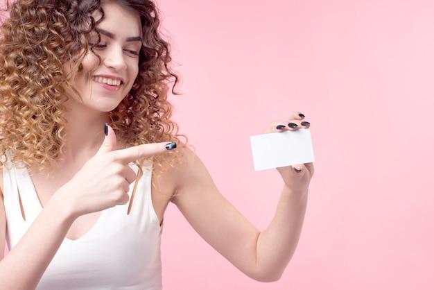 Молодая красивая девушка с вьющимися волосами держит карту в руке и показывает ее. Premium Фотографии
