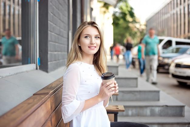 街を歩いて飲む美しい少女は、屋外カフェでコーヒーを奪います。市の朝のシーン。 Premium写真