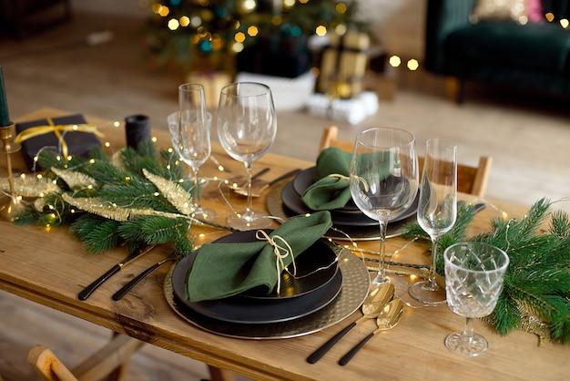 Стол подается на рождественский ужин в гостиной, вид крупным планом, сервировка стола, рождественские украшения Premium Фотографии