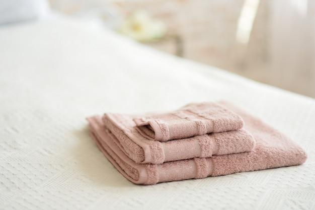 Сложенные полотенца на кровати в номере. Premium Фотографии