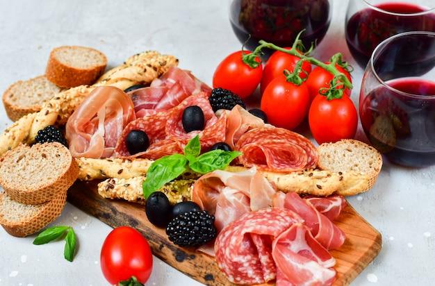 Итальянская закуска с ветчиной, салями, помидоры с оливками брезаола и хлебные палочки гриссини. аперитив счастливый час Premium Фотографии
