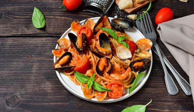 Макароны из морепродуктов спагетти с моллюсками и креветками с мидиями и помидорами в белой тарелке с на деревянном столе. рецепт итальянской кухни. вид сверху Premium Фотографии