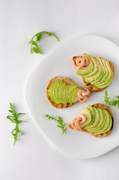 健康的な食事の前菜のコンセプト。ルッコラとエビの白い皿にアボカドトースト。オーバーヘッドショット、垂直。 Premium写真