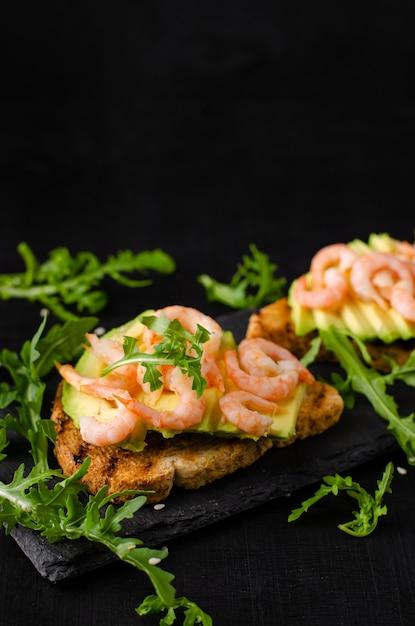 健康的な食事の前菜のコンセプト。ルッコラと黒の背景にエビのアボカドトースト。コピースペース、垂直 Premium写真