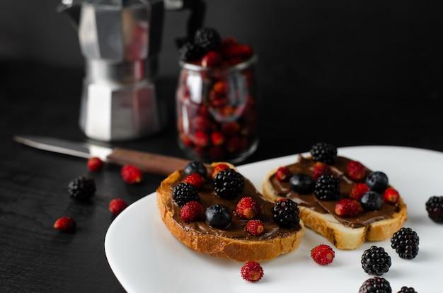 Вкусный сладкий тост со свежими ягодами и кофе на завтрак на темном фоне. Premium Фотографии